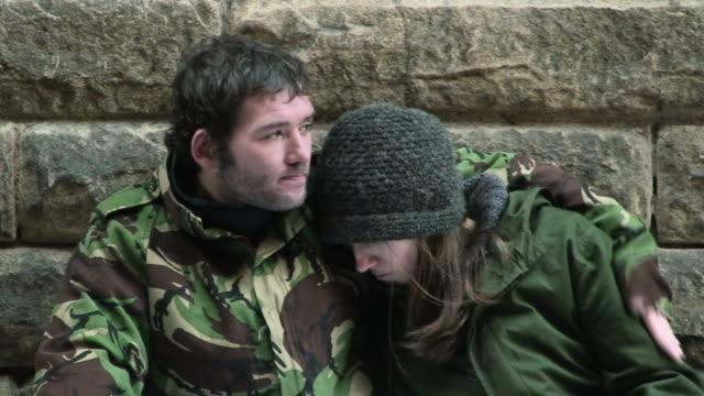 Homeless couple sitting on street video