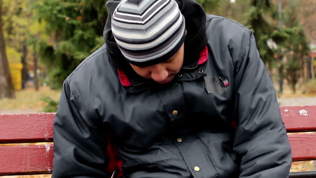 Homeless drunk sleeping on bench in park, unhappy life of poor addicted man video