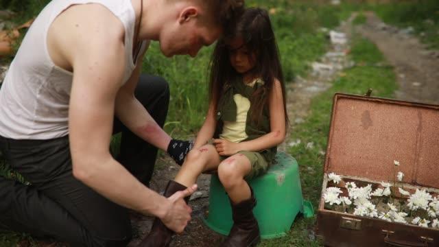 il padre senza tetto è seduto su una discarica e sta ispezionando la ferita sulla gamba di sua figlia. - ucraina video stock e b–roll
