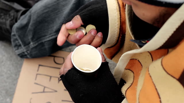 Homeless male counting change, alone in big city, poverty, depression, close-up video