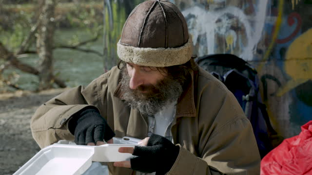 Homeless man eating leftover food given to him by a stranger Homeless man in his 40s or 50s eating leftover food given to him by a stranger out of a white togo container leftovers stock videos & royalty-free footage