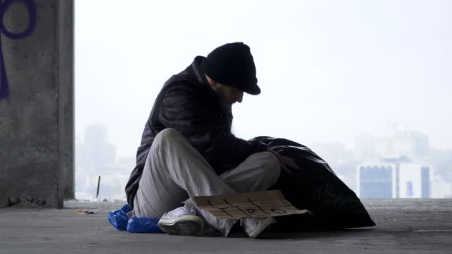 Homeless man goes to sleep on the garbage bag, urban background video
