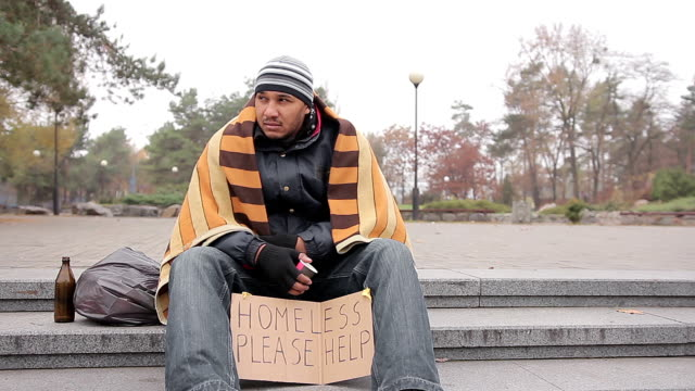 Homeless man in shabby clothes sitting in city park with sign asking for help video