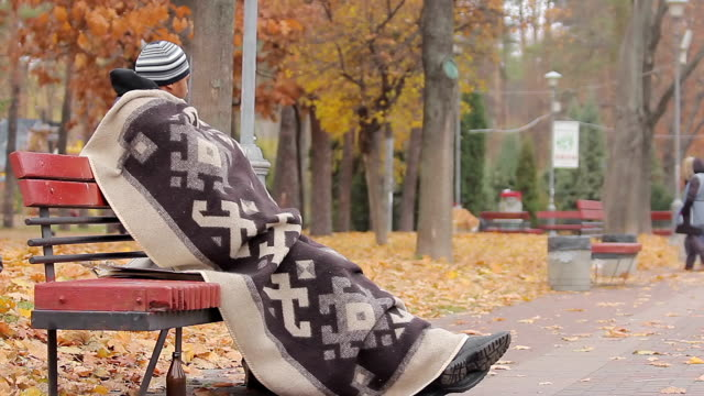 Homeless man sitting on bench with sad face, looking at people in autumn park video