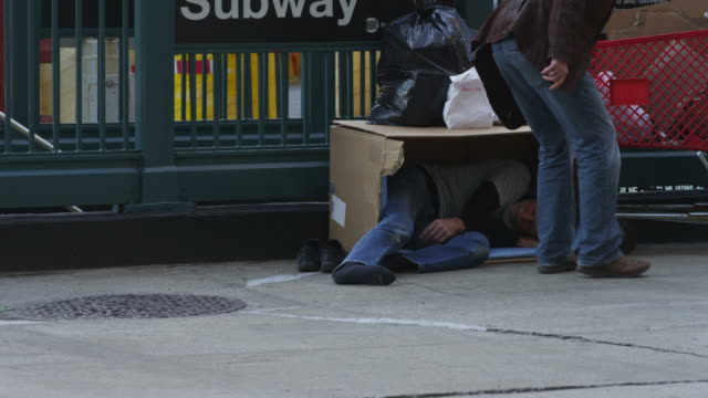 homeless man sleeping on street by subway station - homelessness stock videos & royalty-free footage