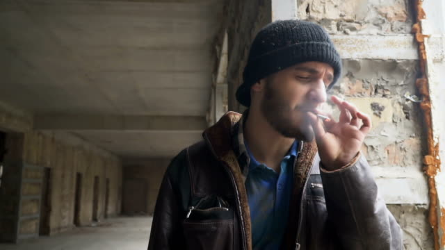 Homeless man smokes cigarette in abandoned building video