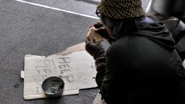 Homeless old man in dirty clothes eating bread while sitting on the street and asking for help Homeless old man in dirty clothes eating bread while sitting on the street and asking for help homeless person stock videos & royalty-free footage