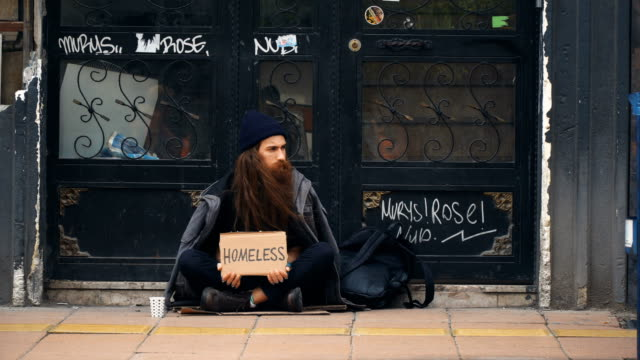 Homeless Person Holding 'Homeless' Cardboard and Begging on Crowded Street 4K, 29.97P, Wide Shot homeless shelter stock videos & royalty-free footage
