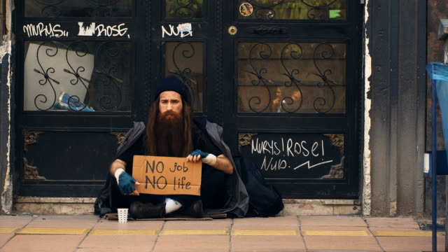 Homeless Person Holding 'No Job No Life' Cardboard and Begging on Crowded Street 4K, 29.97P, Wide Shot homeless shelter stock videos & royalty-free footage
