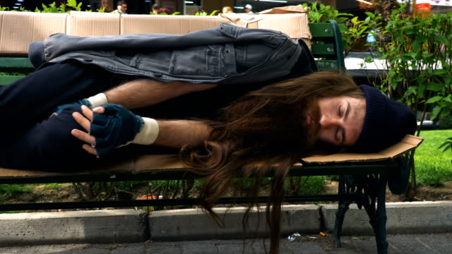 Homeless Person Sleeping on Bench 4K, 29.97P, Sliding Shot homeless shelter stock videos & royalty-free footage