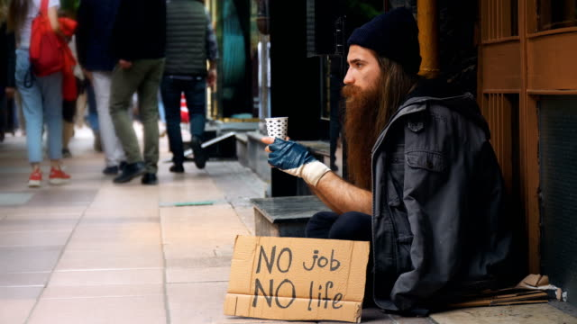 Homeless Person with 'No Job No Life' Cardboard and Begging on Crowded Street 4K, 29.97P, Wide Shot homelessness stock videos & royalty-free footage