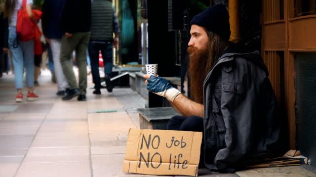 집 없는 사람 ' 아무 일 없음 생활 ' 골 판지와 붐비는 거리에 구걸 - unemployment 스톡 비디오 및 b-롤 화면