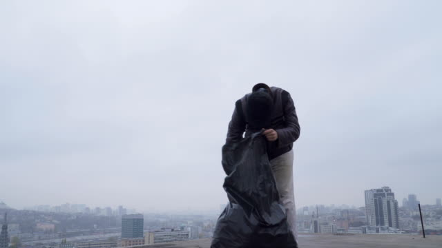Homeless searches something in the garbage bag at urban background video