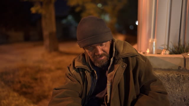Homeless sick man sitting on the street at night. Lonely cold beggar Homeless sick man sitting on the street at night. Lonely cold beggar living on the streets for many years. homeless person stock videos & royalty-free footage
