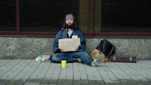 Homeless with cardboard on street video