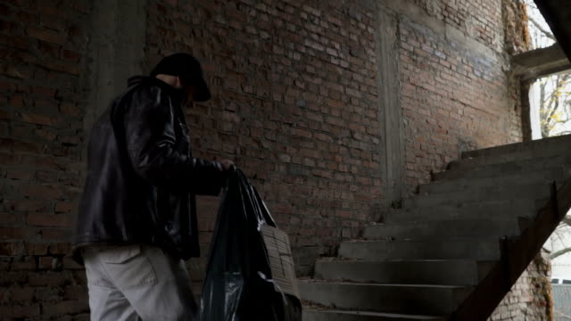 Homeless with garbage bag up stairs in abandoned building video