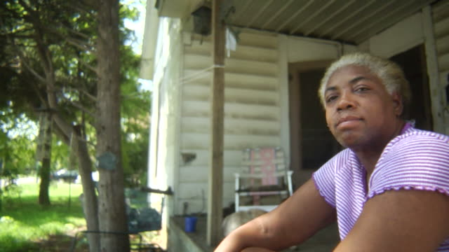 Homeless woman on porch The african american woman has a look of despair as she sits on the porch of a run down home. porch stock videos & royalty-free footage
