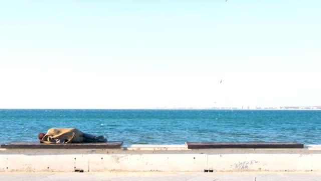 海水辺のベンチで寝ているホームレス女性。 - ベンチ点の映像素材/bロール