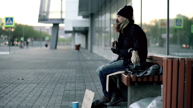 Homeless young man eating sandwich and drinking alcohol from paper bag on bench at city street in evening video