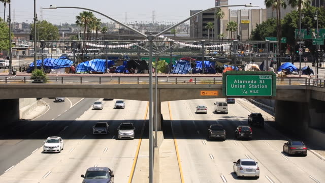 Homelessness Los Angeles, California / USA - May 1, 2020: Traffic from the 101 Freeway passes underneath a homeless encampment on Main Street in Downtown Los Angeles. homelessness stock videos & royalty-free footage