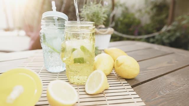 vídeos de stock e filmes b-roll de homemade fresh lemonade with mint and ice. making two lemon cocktail, lifestyle. outdoor shot in summertime. - limonada tradicional