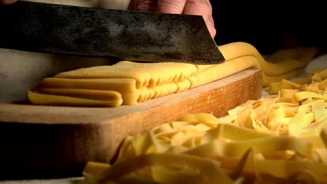 pastas frescas caseras: pasta de corte con un cuchillo tradicional en una mesa de madera - vídeo