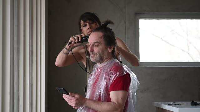 vídeos y material grabado en eventos de stock de diy pareja de corte de pelo casero durante covid-19 - stay home