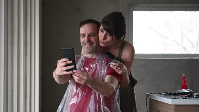 vídeos de stock e filmes b-roll de diy homemade haircut couple during covid-19 - covid hair