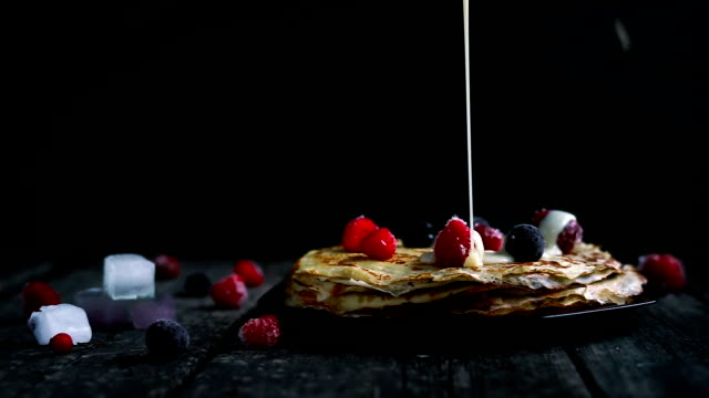 Homemade pancakes with flowing condensed milk sauce served on plate with strawberry and cherry with ice cream on vintage wood table video