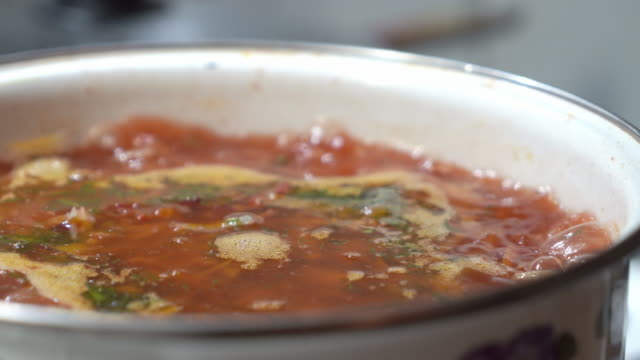 Homemade red borscht boiling in large soup pot on stove.