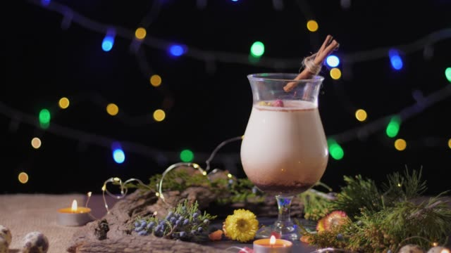 homemade traditional Christmas eggnog drink in glass with ground nutmeg and cinnamon decorating with christmas tree and lights, preparing for celebrating festive holiday season