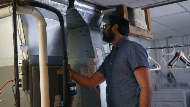 A homeowner is puzzled and frustrated over why his furnace is't working A homeowner is puzzled and frustrated over why his furnace is't working furnace stock videos & royalty-free footage