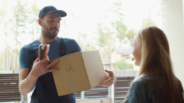 房主打開送貨上門的人, 並收到包裹後, 簽署了送貨設備。 - postal worker 個影片檔及 b 捲影像