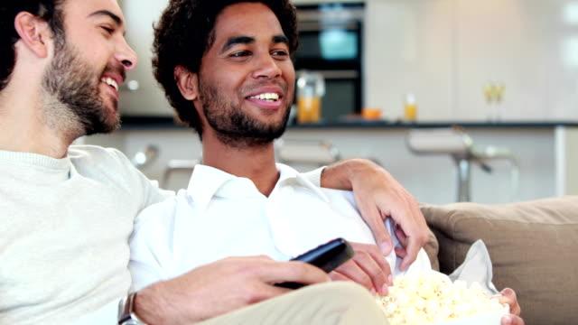 coppia omosessuale uomo mangiare popcorn insieme - coppia gay video stock e b–roll