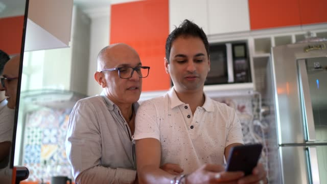 Homosexual couple using smartphone at home