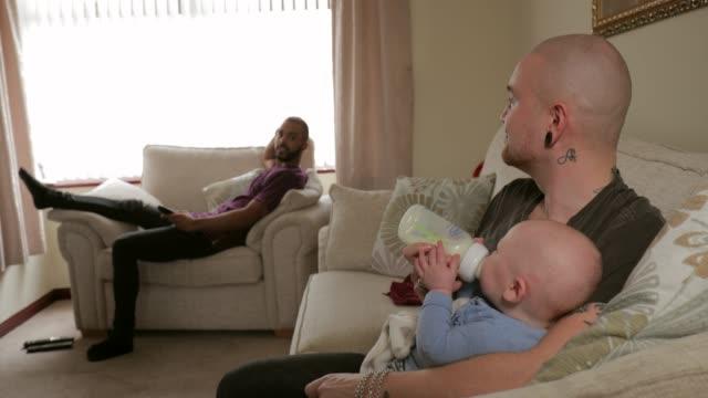 homosexual guy feeding the baby - настоящая жизнь стоковые видео и кадры b-roll