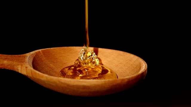 Honey dripping from a wooden honey dipper on black, slow motion video