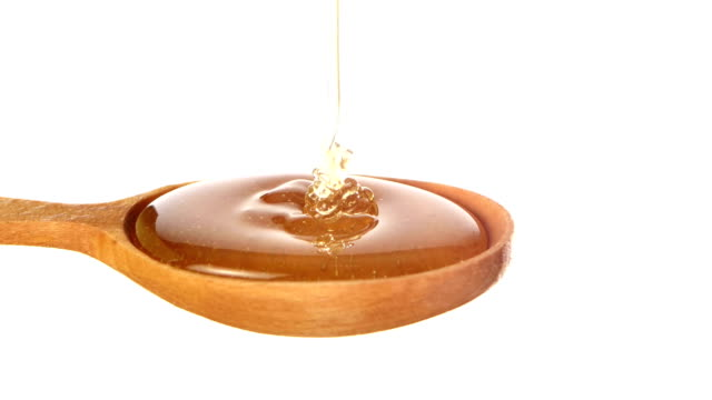 Honey dripping from a wooden honey dipper on white video