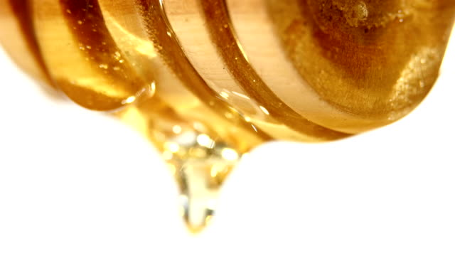 Honey dripping from a wooden spoon, on white video