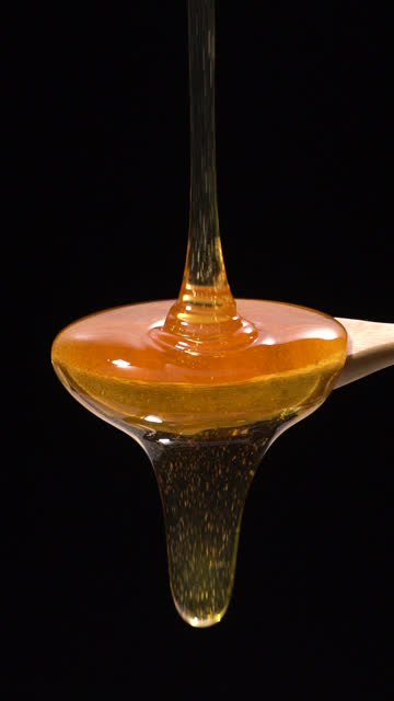 (Slow motion and Vertical) Honey falling from a wooden spoon