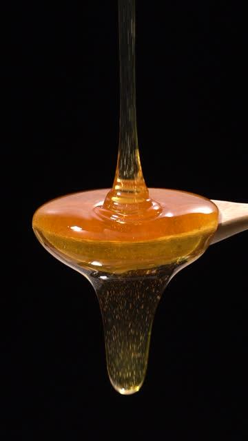 vídeos y material grabado en eventos de stock de (cámara lenta y vertical) miel cayendo de una cuchara de madera - pegajoso