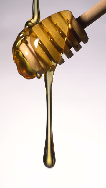 (Slow motion and Vertical) Honey flowing from a wooden honey dipper