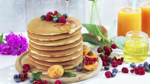 Honey is poured on a stack of pancakes. video