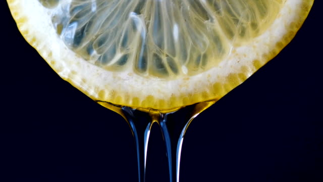 honey on half lemon dripping on black background - gusto aspro video stock e b–roll
