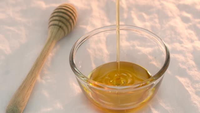 мед, льется в стеклянную миску - white background стоковые видео и кадры b-roll