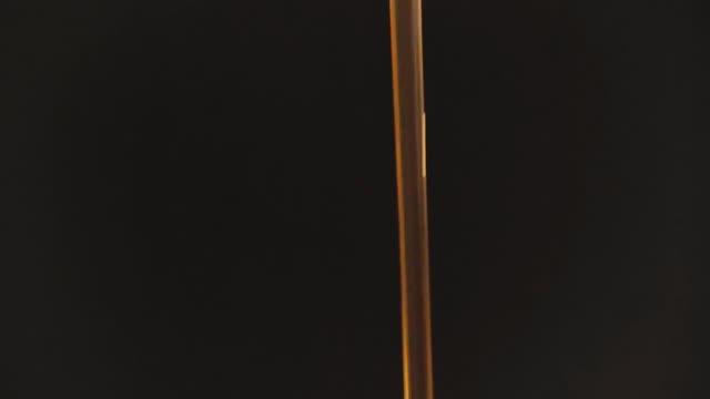 vídeos y material grabado en eventos de stock de jarabe de miel que vierte en el tazón, cámara lenta y fondo negro. - pegajoso