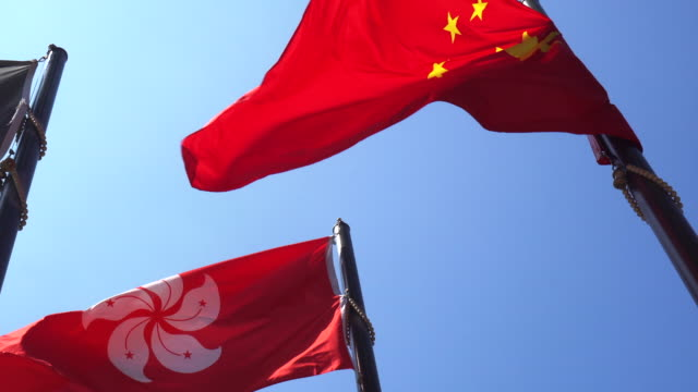 hong kong and mainland china red flags in blue sky. internal political affair conflict - hong kong video stock e b–roll