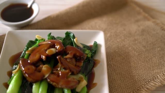 vidéos et rushes de hong kong chou frisé légumes frits dans une sauce d'huître  - bivalve