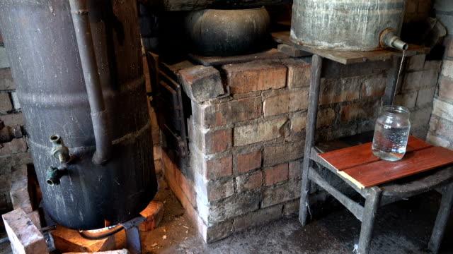 hooch alcohol flow in jar and distillation boiler heat on fire video