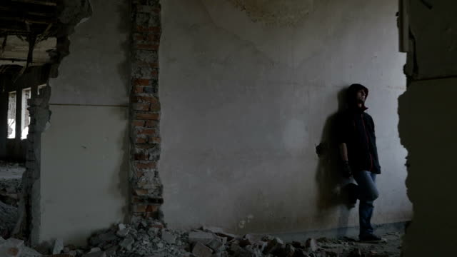 Hooded depressed young man sitting in an abandoned building video